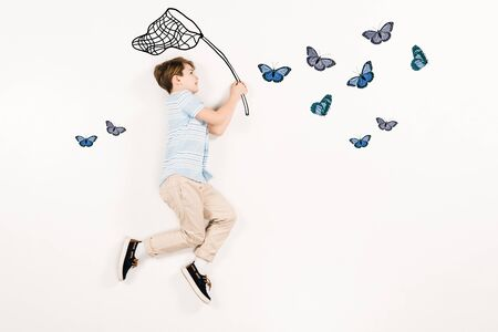 Top view of cheerful kid holding butterfly net near butterflies isolated on a white background