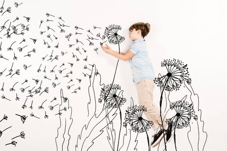 Top view of kid blowing dandelion seeds while flying isolated on a white background 스톡 콘텐츠