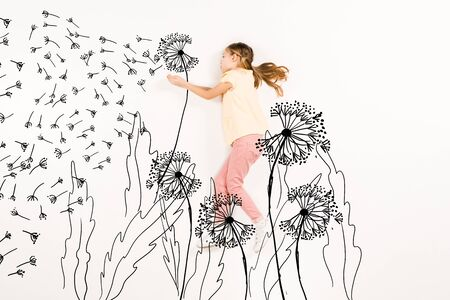 Top view of kid blowing dandelion seeds while flying isolated on a white background 版權商用圖片