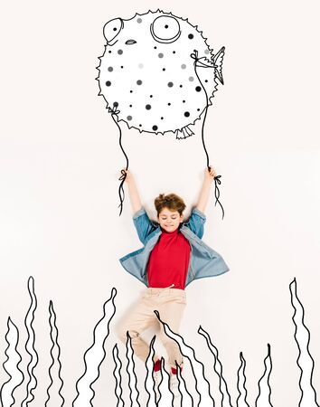 Top view of cheerful kid holding puffer fish isolated on a white background 스톡 콘텐츠