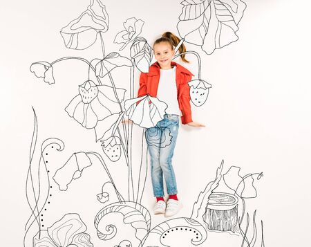 Top view of cute kid smiling near flowers isolated on a white background