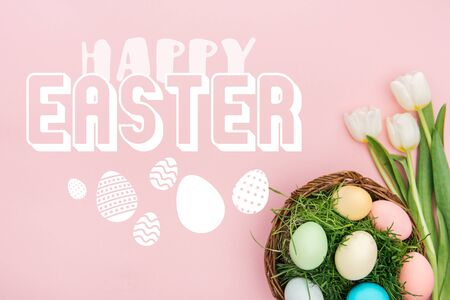 Top view of painted chicken eggs on green grass in wicker basket and white tulips on pink background with white happy Easter lettering