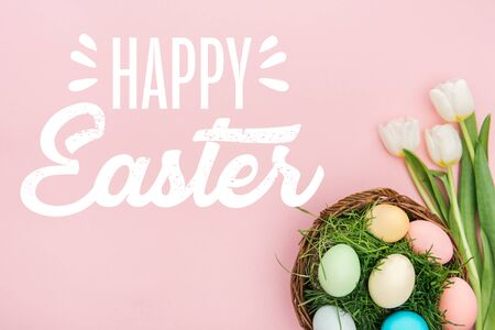 Top view of painted chicken eggs on green grass in wicker basket and white tulips on pink background with happy Easter lettering Stock Photo