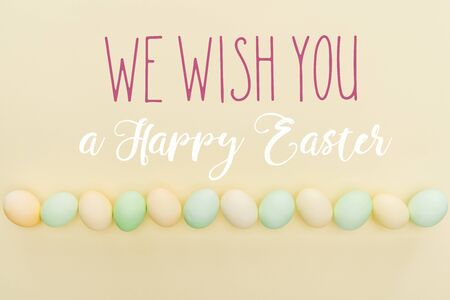 Top view of painted pastel chicken eggs on light yellow background with we wish you a happy Easter lettering Foto de archivo - 124465587