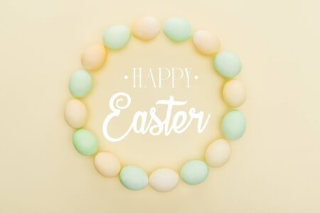 Top view of round frame made of painted chicken eggs on light yellow background with happy Easter lettering