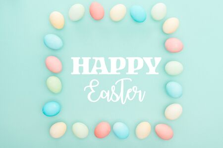 Top view of square frame made of painted chicken eggs on blue background with happy Easter lettering Stockfoto