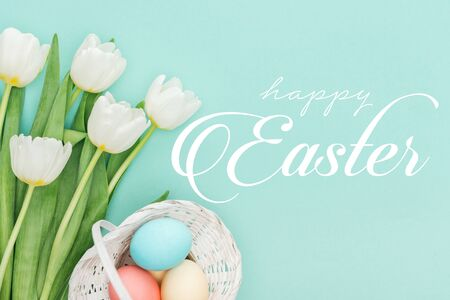 Top view of painted chicken eggs in wicker basket and white tulips on blue background with white happy Easter lettering