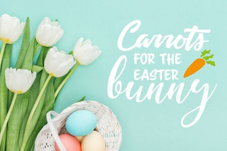 Top view of painted chicken eggs in wicker basket and white tulips on blue background with white carrots for the Easter bunny lettering Stock Photo