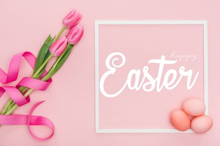 Top view of pink tulips bouquet with ribbon and painted eggs near frame with white happy Easter lettering on pink background