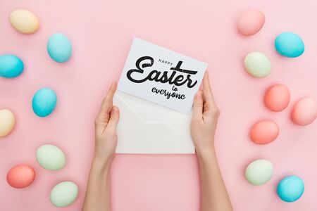 cropped view of woman holding envelope and greeting card with happy Easter to everyone lettering near multicolored painted chicken eggs on pink background