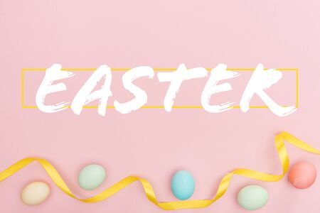 Top view of painted multicolored chicken eggs and satin ribbon on pink background with Easter lettering
