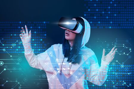 Excited young woman in vr headset gesturing near glowing data illustration on dark background