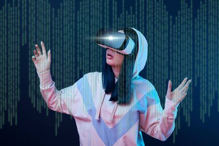 Excited young woman in vr headset gesturing near data illustration on dark background