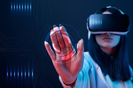 Selective focus of young woman in virtual reality headset pointing with hand at cyber illustration on dark background