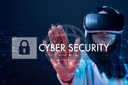 Selective focus of young woman in virtual reality headset pointing with hand at cyber security illustration on dark background Reklamní fotografie