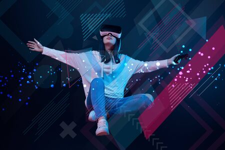 Young woman in virtual reality headset with joystick flying in air among glowing data illustration on dark background