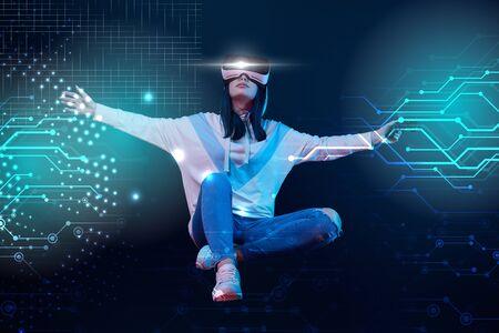 Junge Frau in Virtual-Reality-Headset mit Joystick und ausgestreckten Händen, die in der Luft zwischen leuchtenden Datenillustrationen auf dunklem Hintergrund fliegen
