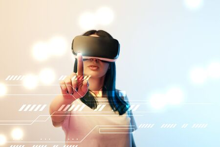 Young woman in virtual reality headset pointing with finger at glowing network illustration on beige and blue background