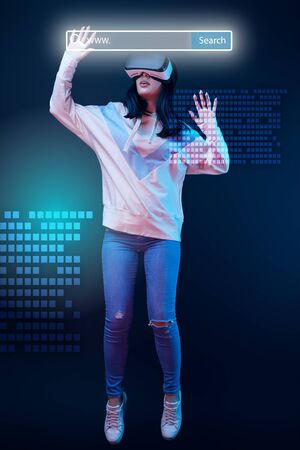 Young excited woman in virtual reality headset levitating in air among glowing data illustration on dark background with search bar above head 스톡 콘텐츠