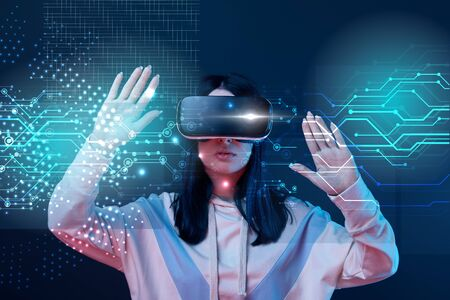 Young woman in virtual reality headset gesturing among glowing cyber illustration on dark background Stock Photo