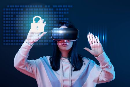 Young woman in virtual reality headset gesturing among glowing cyber security illustration on dark background