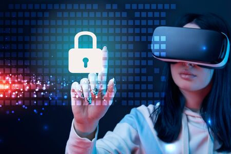 Selective focus of young woman in virtual reality headset pointing with finger at glowing cyber security illustration on dark background Stock Photo