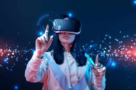 Woman in virtual reality headset pointing with fingers at glowing cyber illustration on dark background Stock Photo