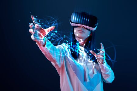 Young woman in vr headset gesturing among glowing cyber illustration on dark background