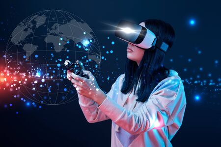 Young woman in virtual reality headset using joystick on dark background with globe illustration 스톡 콘텐츠