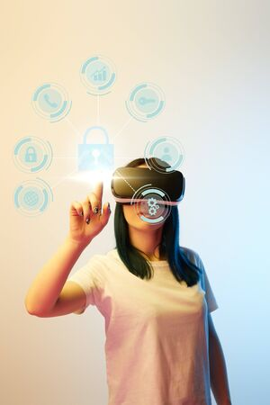 Young woman in virtual reality headset pointing with finger at internet security icons on beige and blue background