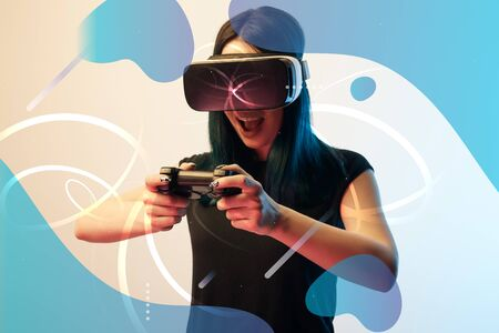 Excited young woman in virtual reality headset using joystick on beige background with abstract blue illustration