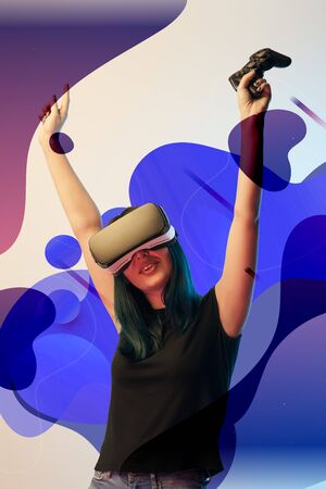 Happy young woman in virtual reality headset with raised hands holding joystick on beige background with abstract purple and blue illustration