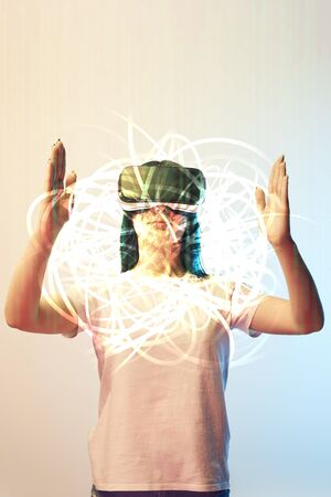 Young woman in virtual reality headset holding glowing abstract illustration on beige and blue background Stock Photo
