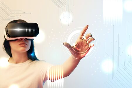 Young woman in vr headset holding circle illustration on beige and blue background Stock Photo