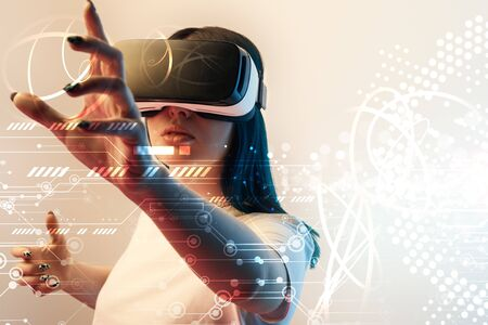 Young woman in virtual reality headset gesturing with hands among glowing cyber illustration on beige background Stock Photo