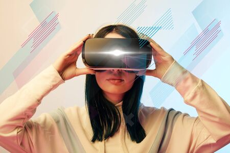 Young woman in virtual reality headset with glowing cyber and abstract illustration on beige and blue background Stock Photo