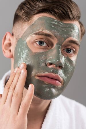 Sad young man touching clay mask isolated on grey background Stock Photo