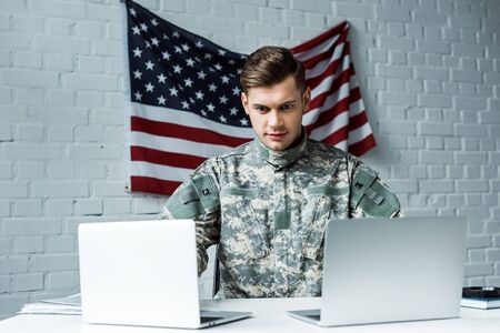 handsome man in military uniform using laptops in office