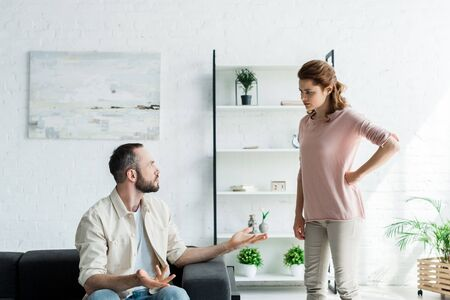 upset man gesturing while looking at woman standing with hand on hip