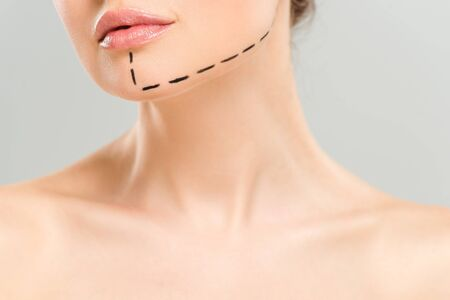 Cropped view of naked woman with marks on face isolated on grey background Фото со стока