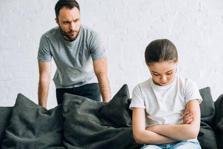 Bärtiger Vater und traurige Tochter sitzen auf dem Sofa und haben Konflikte