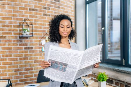 Attractive African American Casual businesswoman reading Business newspaper in loft office