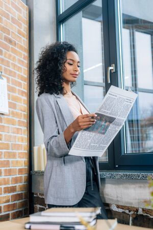 Beautiful African American Casual businesswoman reading Business newspaper in loft office