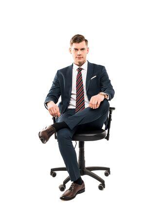 Seguro empresario sentado en una silla y mirando a cámara aislada sobre fondo blanco. Foto de archivo