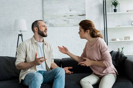 upset woman gesturing and looking at bearded man talking while sitting on sofa