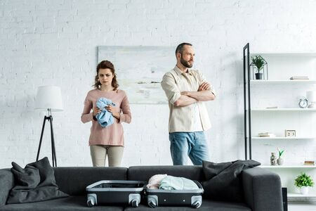 offended man standing with crossed arms near upset woman at home Stock Photo