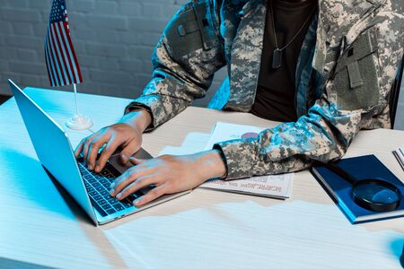 cropped view of military man typing on laptop in office