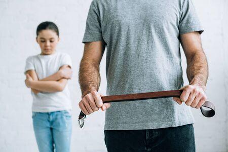 Ausgeschnittene Ansicht von Vater mit Gürtel und verärgerter Tochter zu Hause