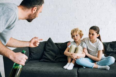 Vue recadrée d'un père alcoolique avec de la bière et des enfants contrariés sur un canapé