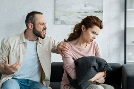 irritated man touching shoulder of offended woman at home